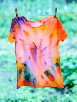 T-shirt im tie dye-stil gemalt wird an einem seil getrocknet.