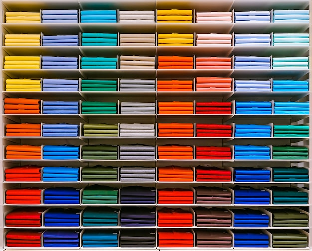 T-shirts in verschiedenen farben sind ordentlich in einer reihe auf den ladenregalen gestapelt.
