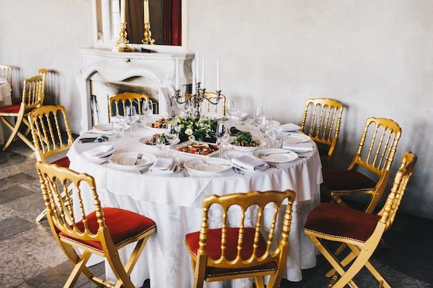 Tabelle diente mit den geschmackvollen tellern, kerzenständer und weißem tischbesteck, verziert für hochzeitsfeierereignis im luxusrestaurant