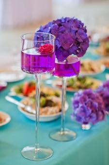Tabelle im restaurant verziert mit purpurroten blumen, hochzeitsabendessen