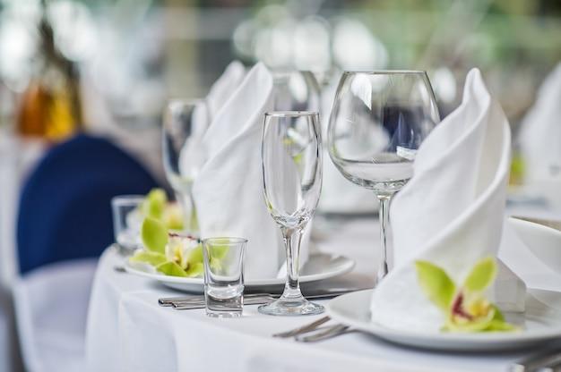 Tabelle mit gläsern, tellern und weißen servietten, grüne blume, abendessen im restaurant
