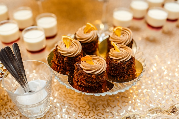 Tabelle mit süßigkeiten und leckereien für die hochzeitsfeier, dekoriert dessert tisch. leckere süßigkeiten am bonbonbuffet. desserttisch für eine party. kuchen, muffins.