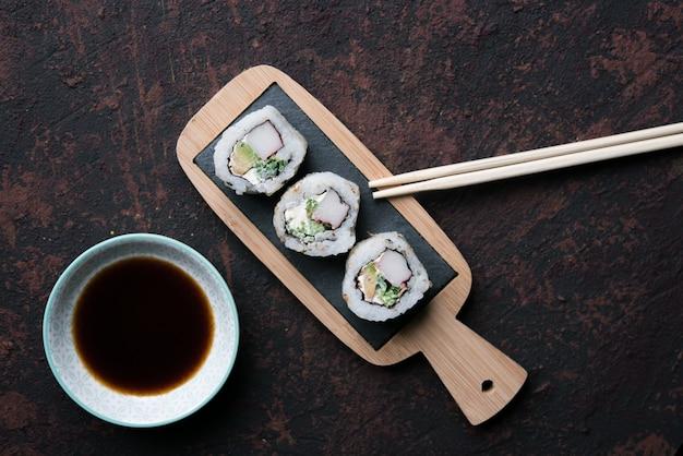 Tabelle mit sushi und essstäbchen mit schüssel sojasoße