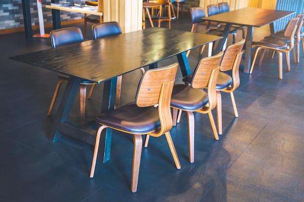 Tabelle und hölzerne stühle in einer modernen kaffeestube.