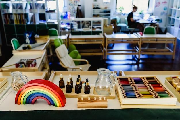 Tabelle und regale mit montessori materical, bunter regenbogenbogen im klassenzimmer.