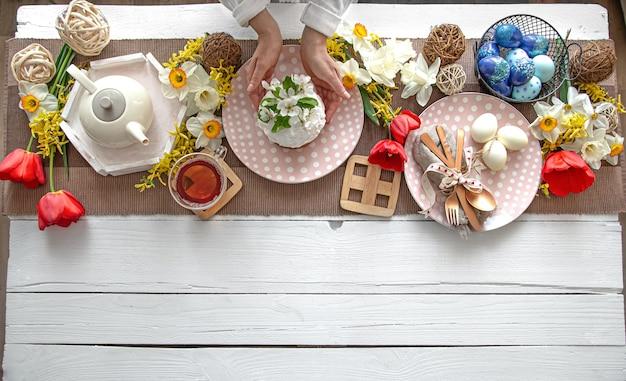 Tabelleneinstellung für die osterferien. tee, hausgemachter kuchen, eier und blumen auf einem holztisch kopieren raum.