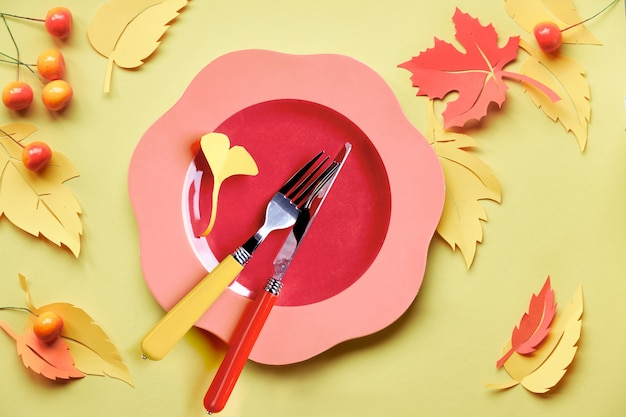 Tabelleneinstellung für herbstfeier. helle plastikplatte auf gelbem papier mit papierherbstlaub