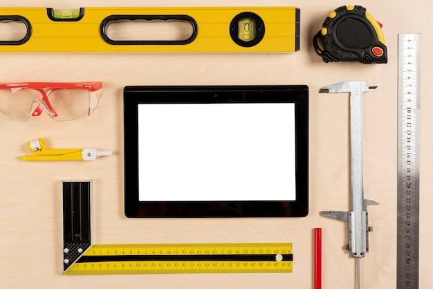 Tablet auf architektenschreibtisch mit werkzeugmodell