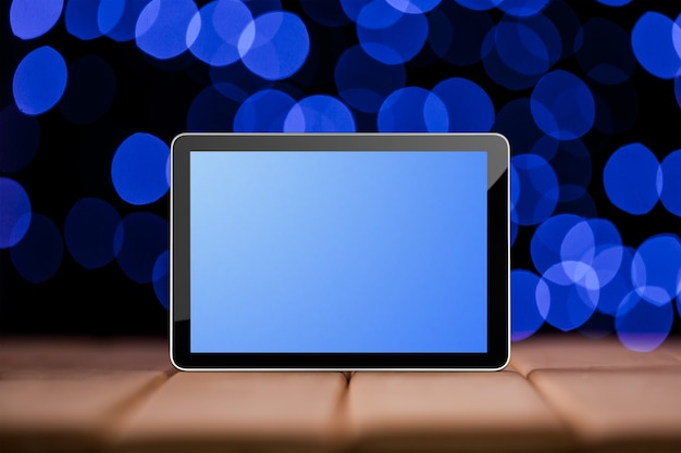 Tablet auf den blauen bokeh-hintergründen. wie ipad