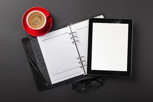 Tablet-computer-gerät auf geschäftsmannschreibtisch und kaffeetasse. draufsicht mit kopienraum