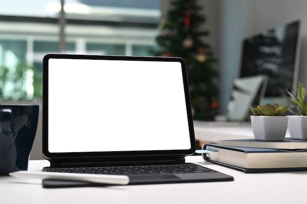 Tablet-computer mit leerem bildschirm, kaffeetasse und notizbuch auf kreativem arbeitsplatz.
