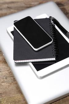 Tablet, computer, smartphone, notizblock und stift auf dem tisch