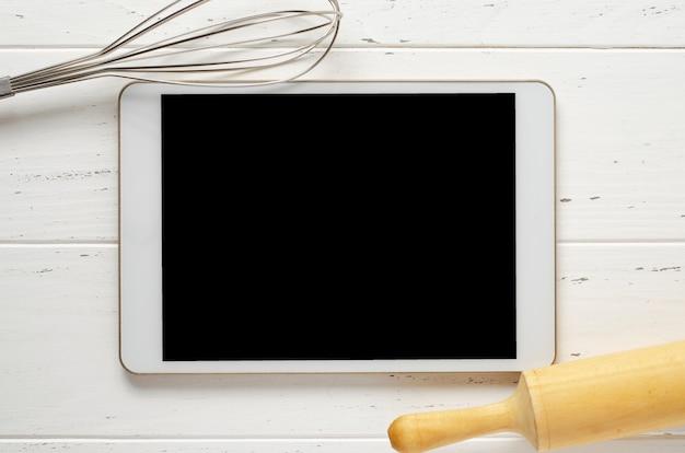 Tablet-computer und kochbatterie auf weißem hintergrund.