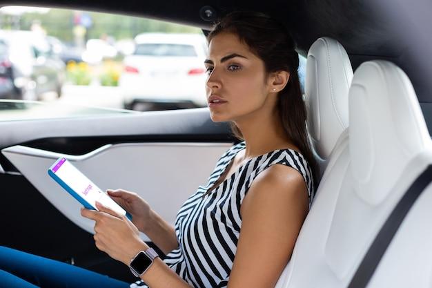 Tablet halten. geschäftsfrau, die eine intelligente uhr mit tablet beim sitzen im auto trägt