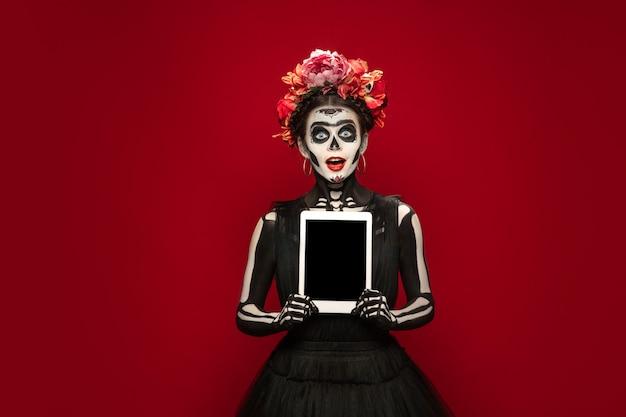 Tablet halten. junges mädchen wie santa muerte saint death oder sugar skull mit hellem make-up. porträt auf rotem studiohintergrund isoliert. feiern von halloween oder tag der toten. copyspace auf dem bildschirm.