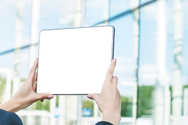 Tablet in den weiblichen händen, vor dem hintergrund des glasgeschäftszentrums.