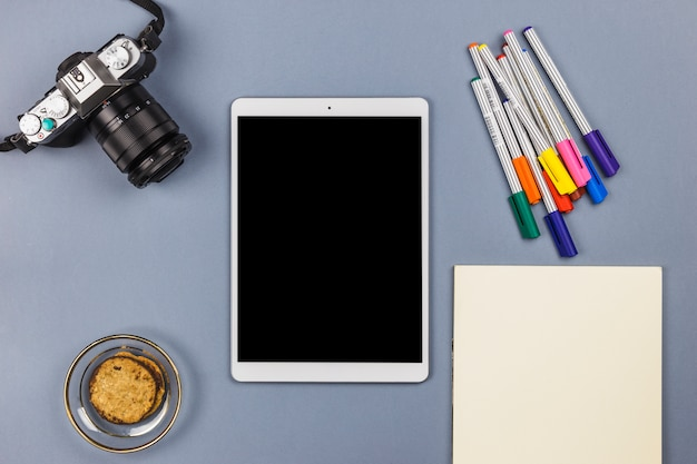 Tablet in der nähe von kamera, papier, keksen in schüssel und filzstiften