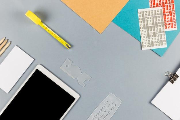 Tablet in der nähe von papier mit clip, tickets, stiften und maßband