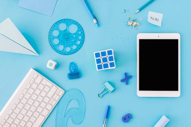 Tablet in der nähe von schulzeug und tastatur