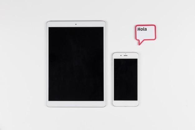 Tablet in der nähe von smartphone und rahmen mit hola inschrift