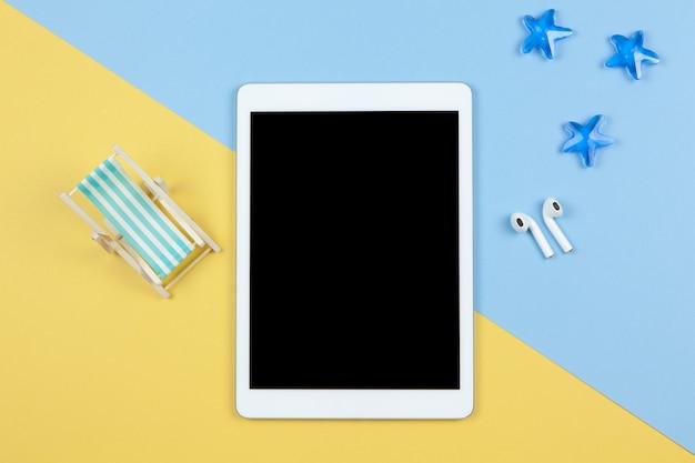 Tablet, kabellose kopfhörer, liegestuhl auf gelbem und blauem hintergrund