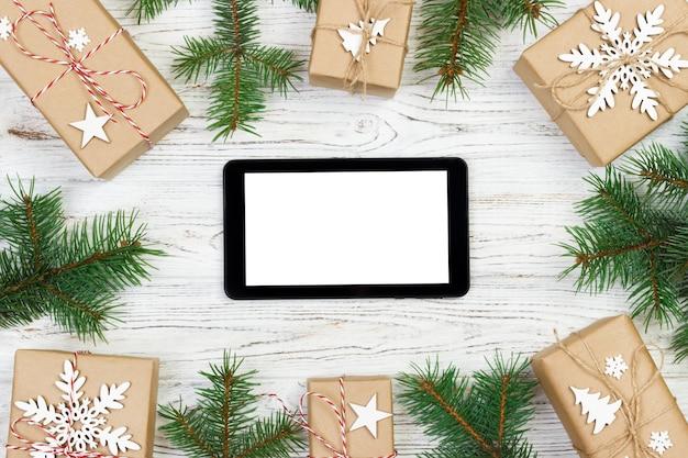 Tablet lokalisiert für die weihnachtszeit stilvoll, geschenkbox und tannenzweige