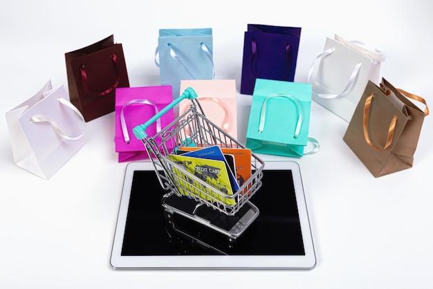 Tablet, mini-einkaufswagen mit kreditkarten und bunten papiertüten isoliert auf weiß, e-commerce