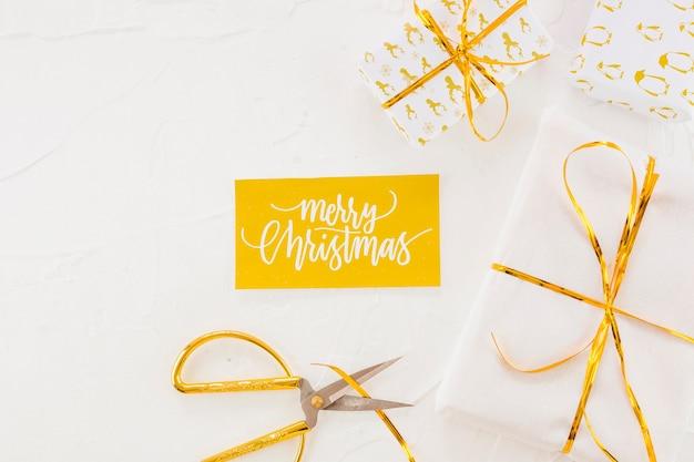 Tablet mit aufschrift der frohen weihnachten nahe präsentkartons