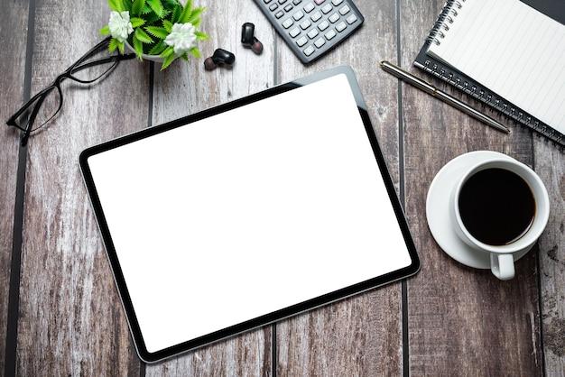 Tablet mit einem leeren bildschirm und einem bürogerät auf einem holztisch.