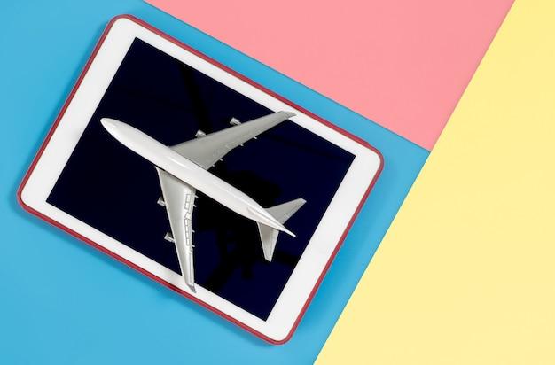 Tablet mit flugzeug für reisekonzept auf blauem gelbem rosa