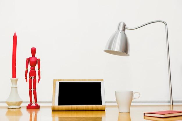 Tablet mit hölzernem mannequin und notizbuch auf tabelle