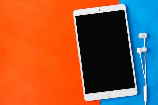 Tablet mit kopfhörer auf orange und blauem hintergrund