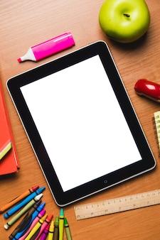 Tablet mit leerem bildschirm mit schulmaterial auf dem tisch, ansicht von oben