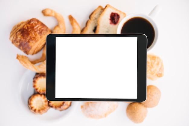 Tablet mit leerem bildschirm über kaffee mit bäckerei