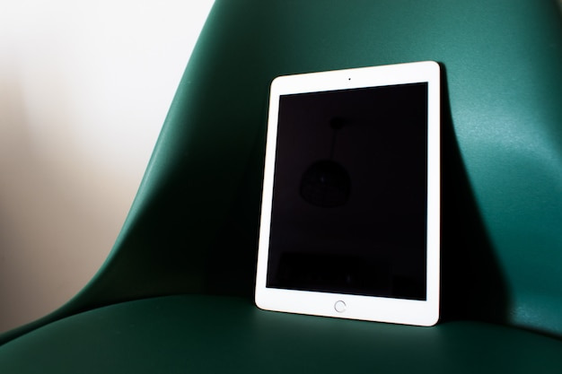 Tablet mit leeren bildschirm auf einem stuhl