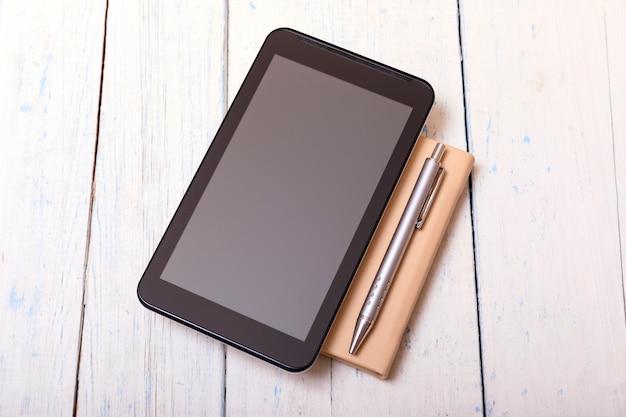 Tablet mit notizbuch auf weißem holztisch und stift shabbi