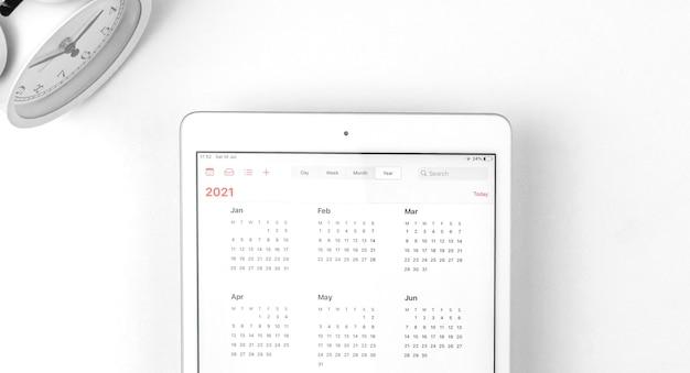 Tablet mit offenem kalender 2021, weißer hintergrundarbeitsplatz mit wecker, geschäftskonzeptfoto
