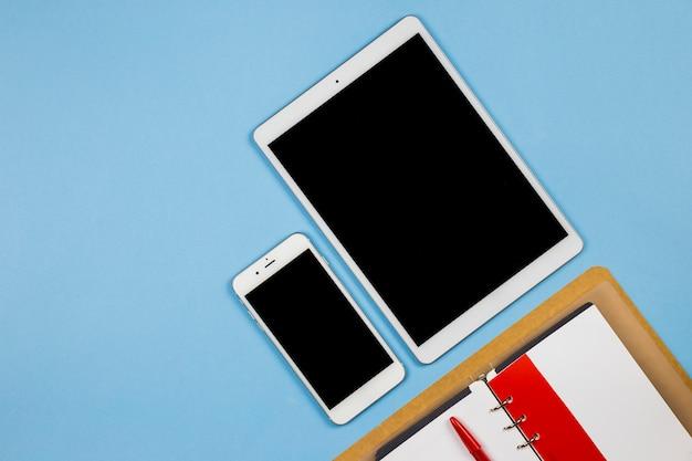 Tablet mit smartphone und notizbuch auf blauer tabelle