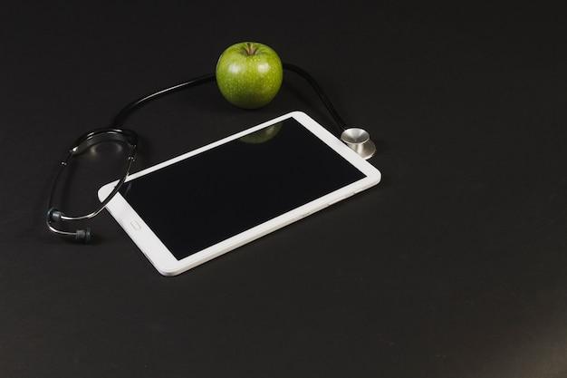 Tablet mit stethoskop und apfel
