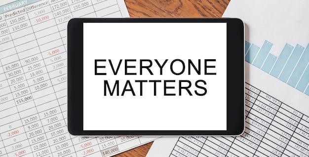 Tablet mit text everybody matters auf ihrem desktop mit dokumenten, berichten und grafiken. geschäfts- und finanzkonzept