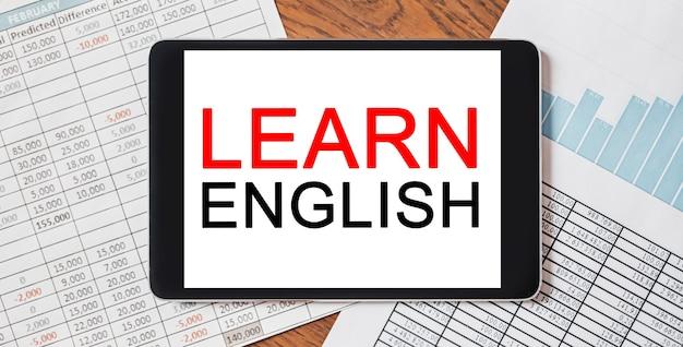 Tablet mit text lernen sie english auf ihrem desktop mit dokumenten, berichten und grafiken. studien- und bildungskonzept