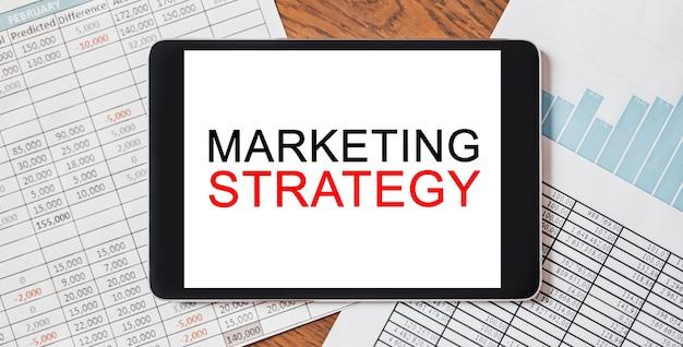 Tablet mit text marketingstrategie auf ihrem desktop mit dokumenten, berichten und grafiken. geschäfts- und finanzkonzept