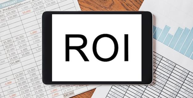 Tablet mit text-roi auf ihrem desktop mit dokumenten, berichten und grafiken. geschäfts- und finanzkonzept