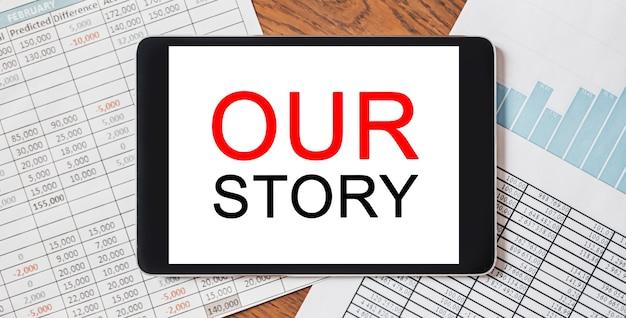 Tablet mit text unsere story auf ihrem desktop mit dokumenten, berichten und grafiken. geschäfts- und finanzkonzept