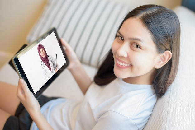 Tablet monitor ansicht über mädchen schulter, eine muslimische ärztin trägt uniform und geben beratung für junge frauen, gesundheitstechnologie konzept