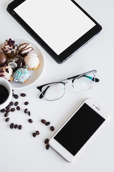 Tablet nahe smartphone, becher, brillen und keksen auf platte