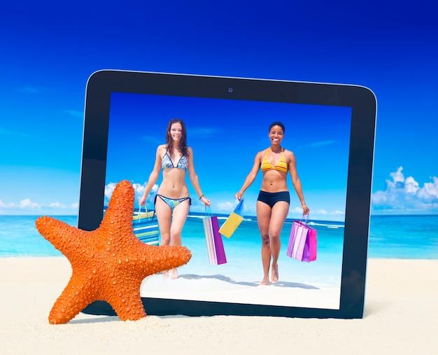 Tablet-pc, der foto von frauen mit einkaufstaschen auf einem tropischen strand macht.
