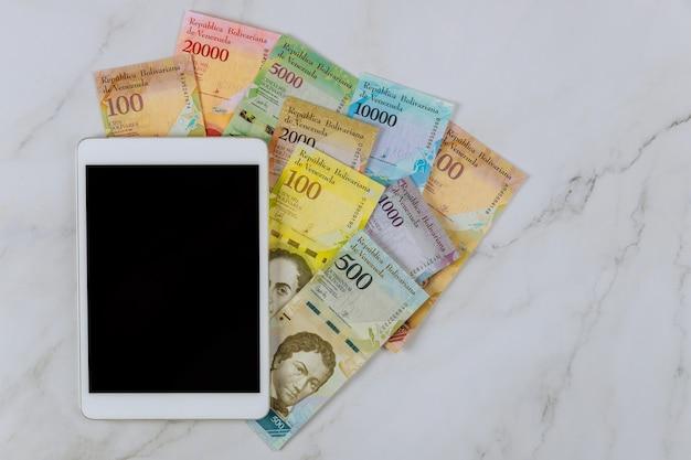 Tablet pc-serie von banknoten mit verschiedenen papierrechnungen währung venezolanischen bolivar auf dem tisch