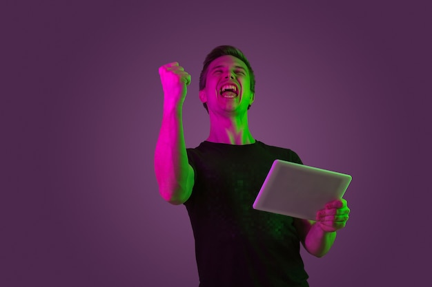 Tablet spielen, videospiele spielen, gewinnen. porträt des kaukasischen mannes auf purpurrotem studiohintergrund im neonlicht. schönes männliches modell im schwarzen hemd. konzept der menschlichen emotionen, gesichtsausdruck, verkauf, anzeige.