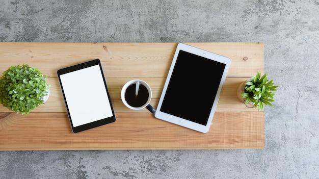 Tablet-startgeschäft des draufsicht-leeren bildschirms und kaffeetasse auf der hölzernen tabelle am morgen